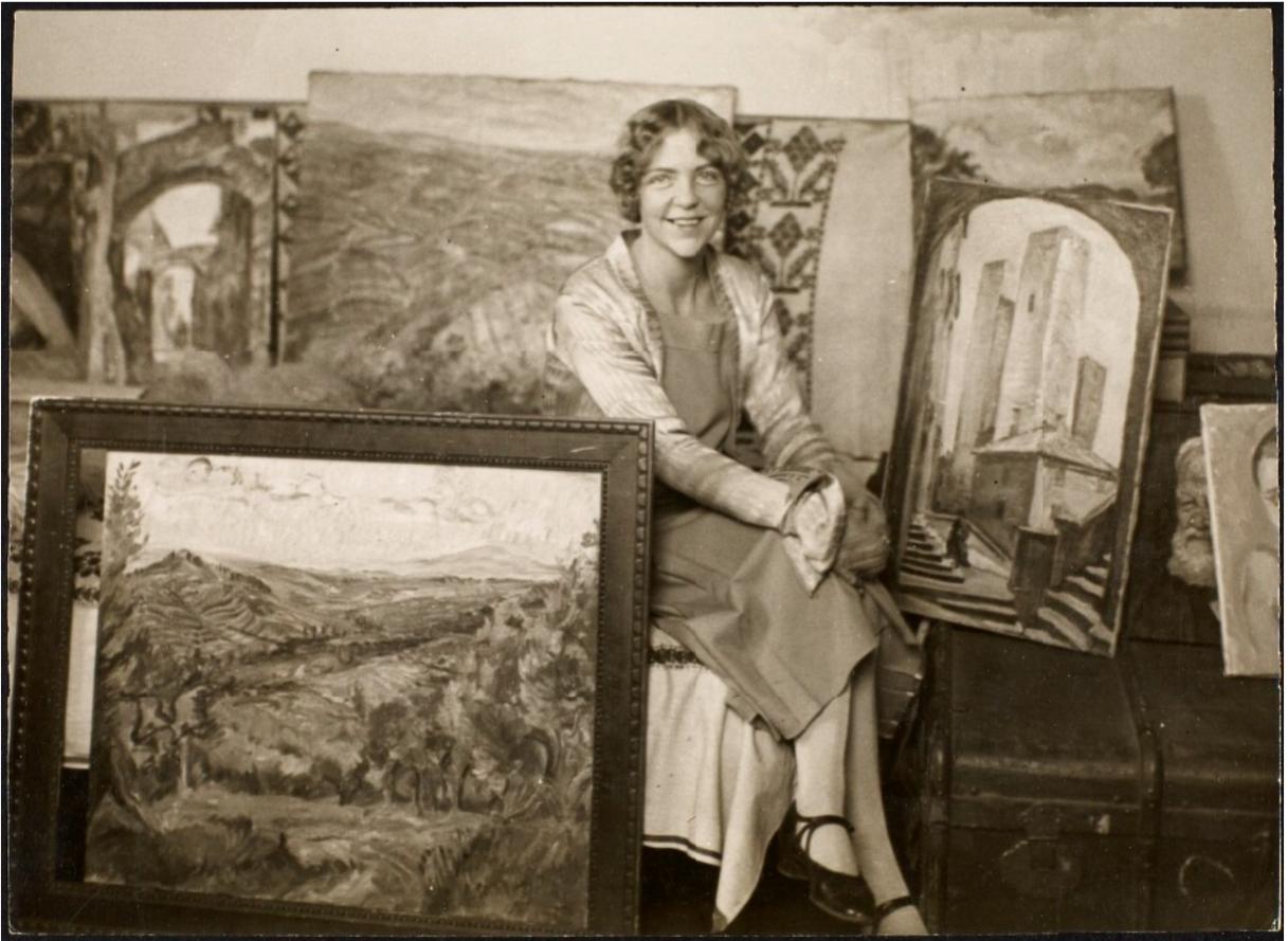 Anne Marie Telmányi (1899-1989) blandt nogle af sine malerier. (Det Kgl. Biblioteks billedsamling).
