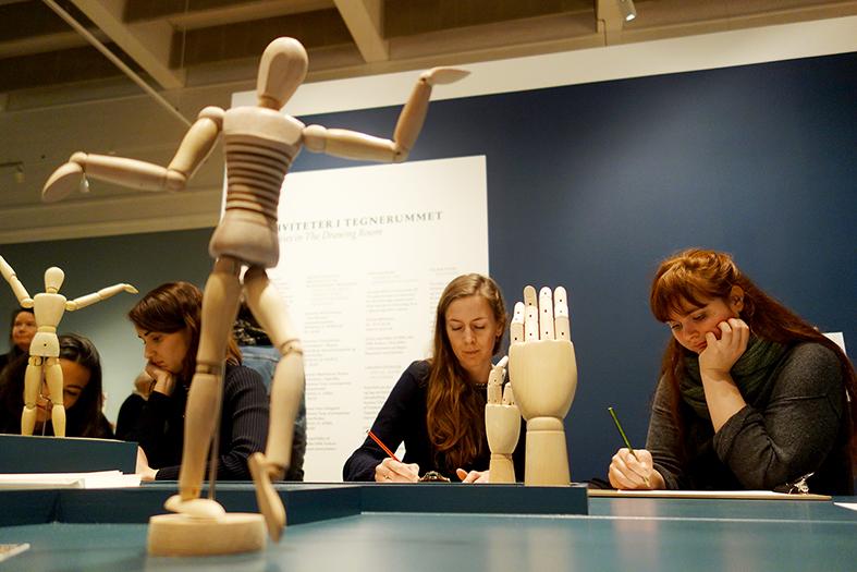En genial idé er det tegneværksted, der er oprettet på udstillingen. Her kan børn og voksne afprøve egne færdigheder med opstillede modeldukker.